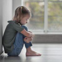 Sad little girl sitting on floor indoors
