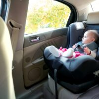 Adorable baby girl sitting and looking outside of a cars window